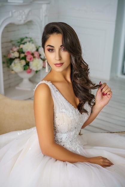 結婚式の美しい若い女性は美しい化粧と髪型幸せな花嫁をドレスアップします。 Premium写真