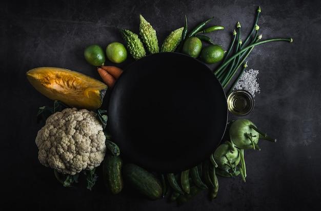 メッセージ用のスペースと黒いテーブルの上の新鮮な野菜 Premium写真