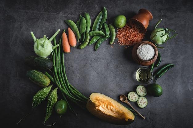 真ん中にテキストメッセージのためのスペースと黒いテーブルの上の新鮮な野菜 Premium写真