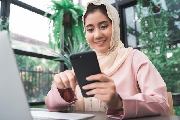 美しい若い笑顔アジアのイスラム教徒の女性は、家庭でリビングルームに座って電話で働く 無料写真