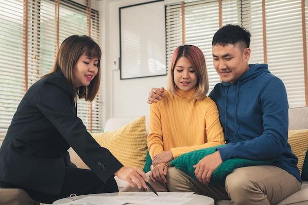 幸せな若いアジアのカップルと不動産業者 無料写真