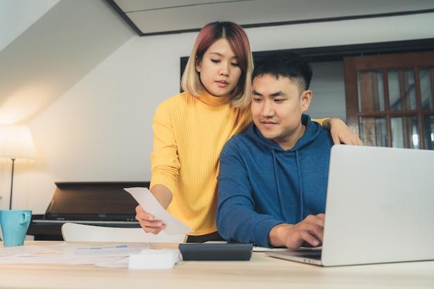 若いアジア人カップルの財政管理、ラップトップコンピュータを使った銀行口座の見直し 無料写真