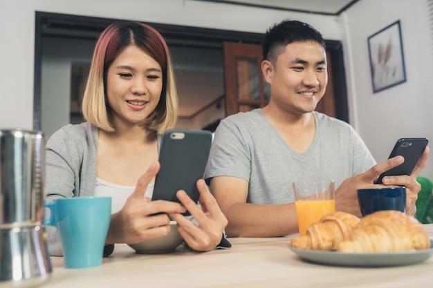 魅力的な若いアジア人のカップルは、新聞や携帯電話のテーブルで気を散らした 無料写真