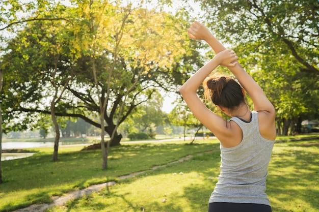 Здоровая молодая азиатская бегунья разминает тело перед тренировкой и йогой Бесплатные Фотографии