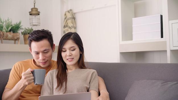 アジアカップルのラップトップを使用して、自宅の居間で暖かい一杯のコーヒーを飲む、甘いカップルを楽しむ 無料写真