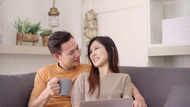 アジアカップルのラップトップを使用して、自宅の居間で暖かい一杯のコーヒーを飲む 無料写真