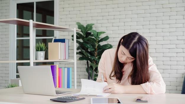 美しい若い笑顔アジア女性自宅のリビングルームの机の上のノートパソコンで作業します。 無料写真