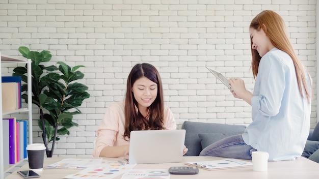 Привлекательные умные творческие азиатские бизнес-леди в элегантной повседневной одежде работают на ноутбуке, сидя Бесплатные Фотографии