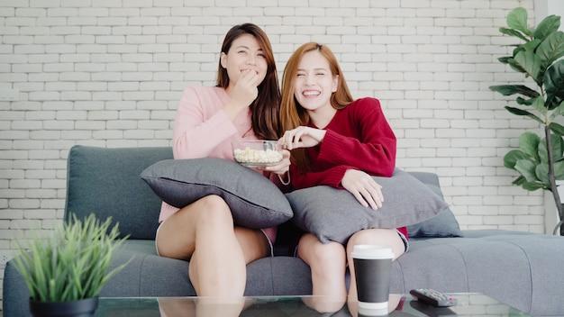 自宅でテレビを見て笑っているとリビングルームでポップコーンを食べてレズビアンアジアカップル、甘いカップル 無料写真