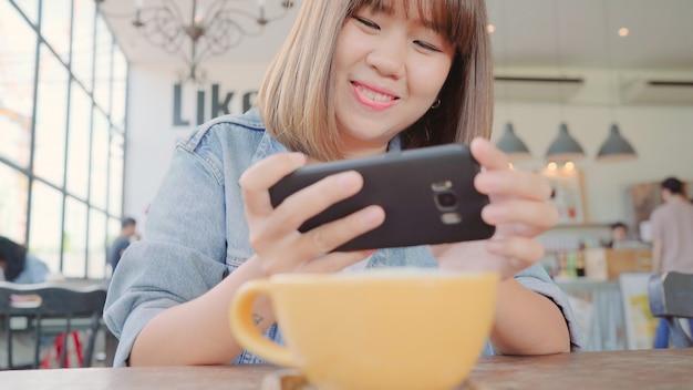 彼女の電話でカフェで緑茶杯を撮影する女性ブロガー。 無料写真