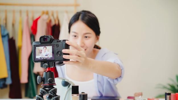 美しさのブロガーは、ビデオを録画するために正面のカメラに座っている美しさ化粧品を提示します。 無料写真