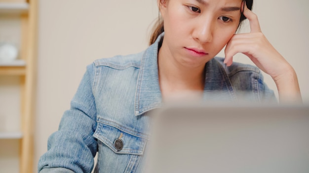 Компьтер-книжка красивой молодой усмехаясь азиатской женщины работая на столе в живущей комнате дома. финансы и калькулятор документа тетради сочинительства бизнес-леди азии в домашнем офисе. Бесплатные Фотографии
