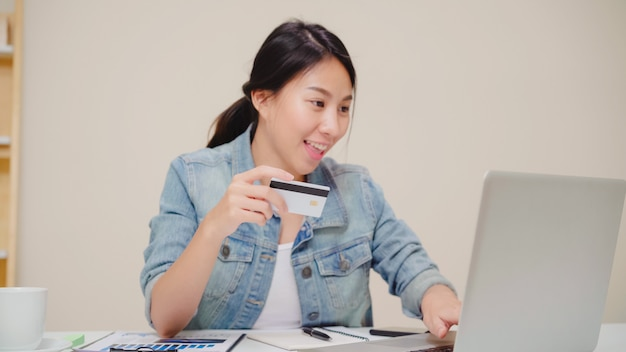 Красивая азиатская женщина используя компьтер-книжку покупая онлайн покупки кредитной карточкой пока носка вскользь сидя на столе в живущей комнате дома. Бесплатные Фотографии