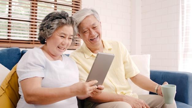Азиатские пожилые пары используя таблетку и выпивая кофе в живущей комнате дома, пары наслаждаются моментом влюбленности пока лежащ на софе когда расслаблено дома. Бесплатные Фотографии