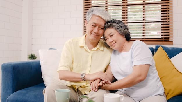 アジアの老夫婦が居間で一緒に服用しながら手を取り合って、幸せな気分を共有し、自宅のソファーに横になってお互いを支え合っています。 無料写真