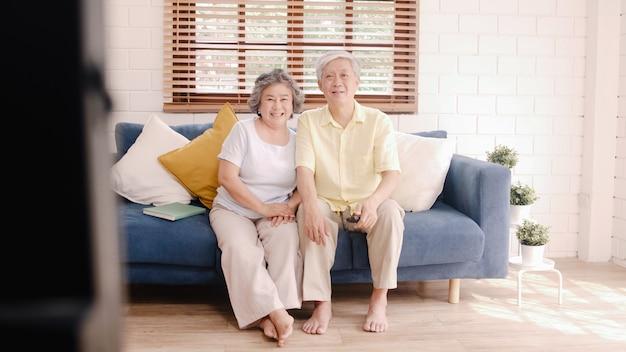 自宅でリビングルームでテレビを見ているアジアの老夫婦、自宅でリラックスしたときに甘いカップルはソファーに横たわっている間愛の瞬間を楽しんでいます。 無料写真