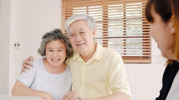 アジアのスマート女性エージェントは、文書、タブレット、ラップトップによって、老夫婦のための健康保険を提供しています。 無料写真
