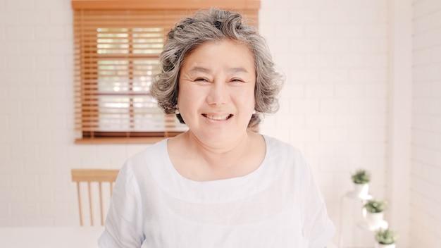 アジアの高齢女性が幸せな笑みを浮かべて、自宅のリビングルームのソファーでリラックスしながらカメラを探しています。家のコンセプトでライフスタイルの年配の女性。 無料写真