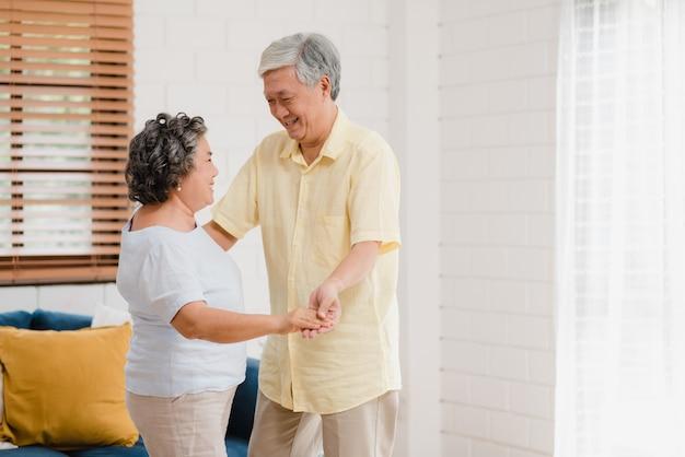 自宅でリビングルームで音楽を聴きながら一緒に踊るアジアの老夫婦、自宅でリラックスしたときに楽しみながら恋人同士を愛するカップル。 無料写真