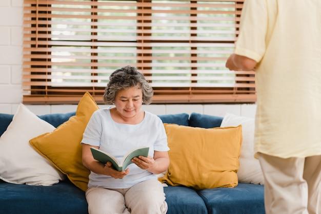 アジアの高齢者女性が自宅の居間で本を読んでいます。中国の女性が自宅でリラックスしたときにソファに横になっています。 無料写真