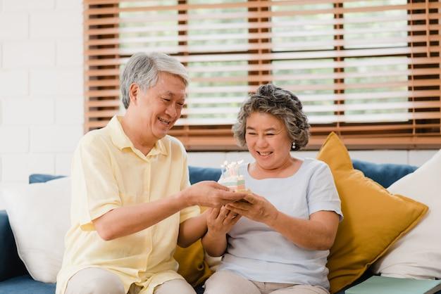 Азиатские пожилые пары укомплектовывают личным составом держать торт празднуя день рождения жены в живущей комнате дома. японская пара наслаждается моментом любви вместе дома. Бесплатные Фотографии