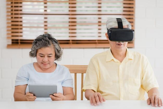 タブレットと仮想現実シミュレータを使用してリビングルームでゲームをしているアジアの老夫婦 無料写真