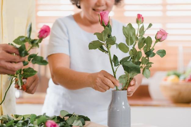 Азиатская пожилая пара делая букет цветет на деревянном столе в кухне дома. Бесплатные Фотографии