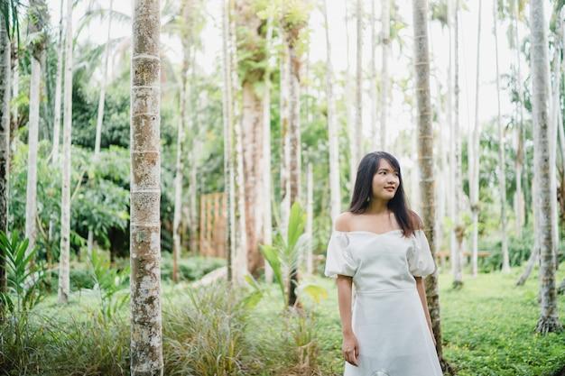 アジアの若い女性は森でリラックスします。美しい女性を使用して幸せな自然の中でリラックスした時間。 無料写真