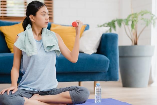 Йога молодой азиатской женщины практикуя в живущей комнате. Бесплатные Фотографии