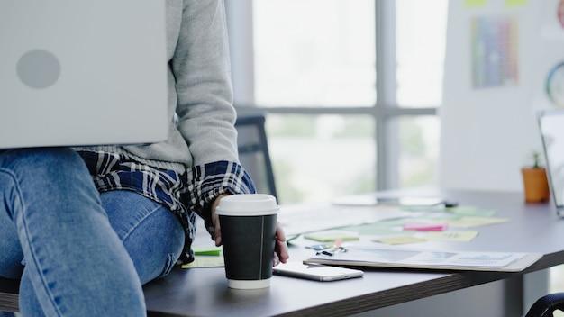 ラップトップを介して彼女のオフィスで働いているプロのアジア女性実業家。 無料写真