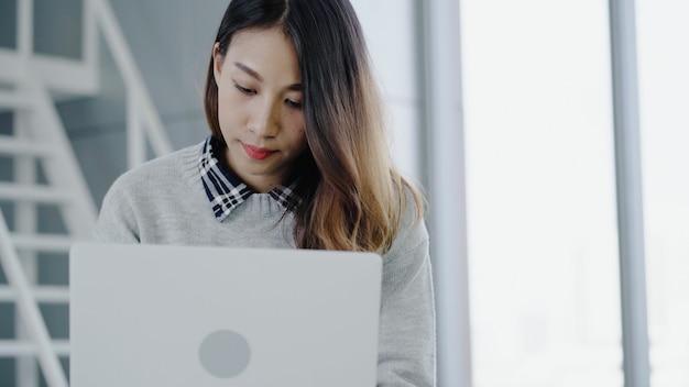 ラップトップを介して彼女のオフィスで働いているプロのアジア女性実業家。現代の職場に座っている間ポータブルコンピューターデバイスを使用して若いアジア女性マネージャー。 無料写真