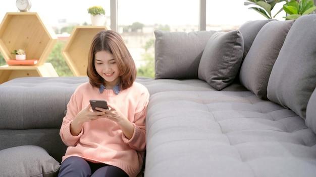 Портрет красивой привлекательной молодой улыбающейся азиатской женщины, используя смартфон, лежа на диване Бесплатные Фотографии