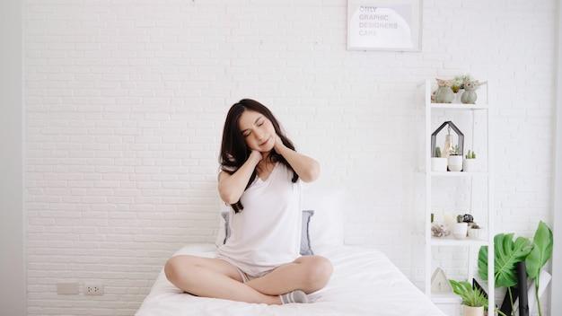 Красивая азиатская женщина протягивая ее тело после того как она просыпает в ее спальне дома. Бесплатные Фотографии