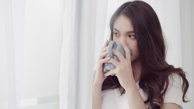 幸せと美しいアジアの女性の笑みを浮かべて、寝室の窓の近くのコーヒーや紅茶のカップを飲みます。 無料写真