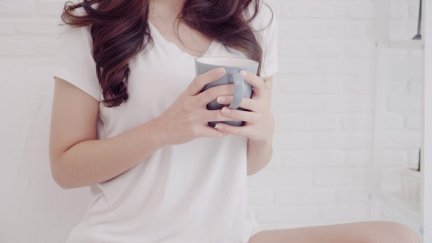 Счастливая красивая азиатская женщина усмехаясь и выпивая чашку кофе или чая на кровати Бесплатные Фотографии