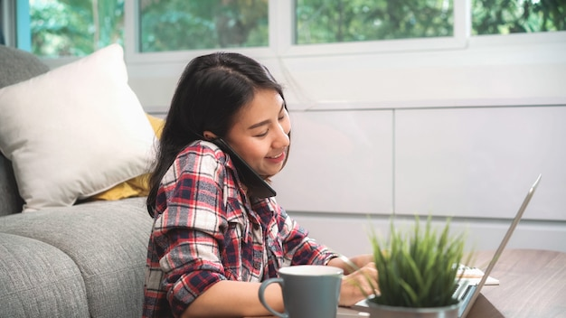 Внештатная азиатская женщина работая дома, женщина дела работая на компьтер-книжке и используя мобильный телефон разговаривая с клиентом на софе в живущей комнате дома. Бесплатные Фотографии