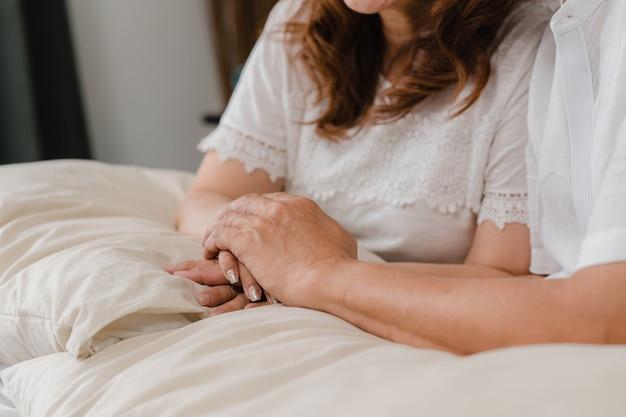 アジアの老夫婦が寝室で一緒に手を取り合って、カップルは幸せな気持ちを共有し、自宅のベッドに横たわっているお互いをサポートします。ホームコンセプトでライフスタイルシニア家族。 無料写真