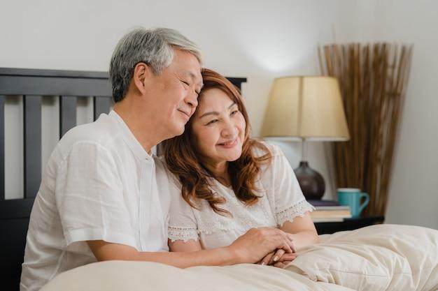 自宅のベッドで話しているアジアシニアカップル。アジアのシニア中国人の祖父母、夫と妻の幸せは、朝のコンセプトで自宅の寝室のベッドに横たわっている間目を覚ます後一緒にリラックスします。 無料写真