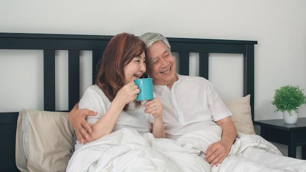 自宅のベッドで話しているアジアシニアカップル。アジアのシニア中国の祖父母、夫と妻の幸せは、朝のコンセプトで自宅の寝室のベッドに横たわっている間目を覚ます後コーヒーを飲みます。 無料写真