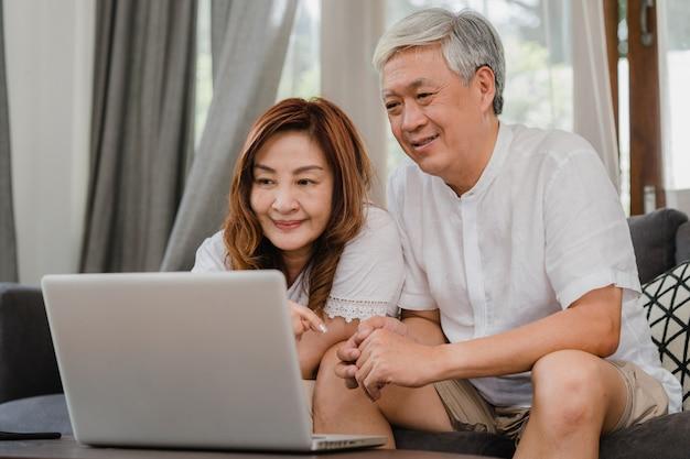 自宅でラップトップを使用してアジアシニアカップル。アジアのシニア中国人の祖父母は、インターネットをサーフィンして、ホームコンセプトのリビングルームのソファーに横たわっている間、ソーシャルメディアをチェックします。 無料写真