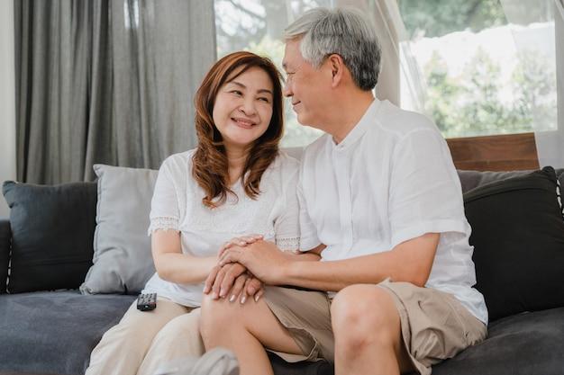 アジアの年配のカップルは自宅でリラックスします。アジアのシニア中国の祖父母、夫と妻の幸せな笑顔が自宅のコンセプトでリビングルームのソファに横たわっている間一緒に話して抱擁します。 無料写真