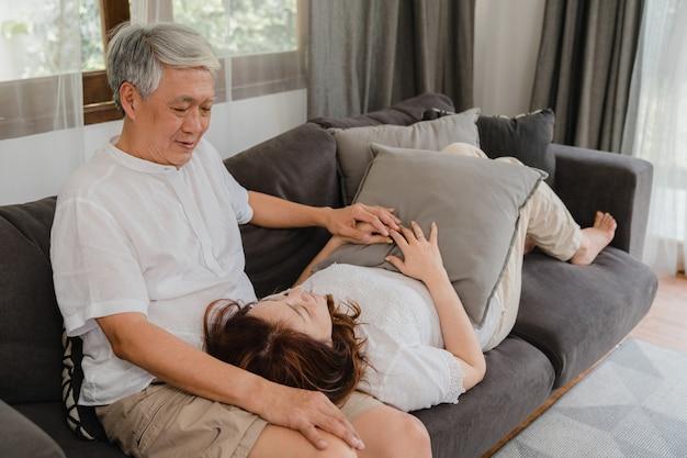 アジアの年配のカップルは自宅でリラックスします。アジアのシニア中国の祖父母、夫の幸せな笑顔の抱擁は、ホームコンセプトのリビングルームのソファーに横たわっている間彼女の妻の膝を横になります。 無料写真