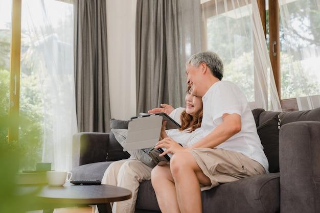 タブレットとリビングルームでゲームをプレイする仮想現実シミュレーターを使用して、アジアの老夫婦、自宅でソファに横たわって一緒に時間を使用して幸せな感じのカップル。ホームコンセプトでライフスタイルシニア家族。 無料写真