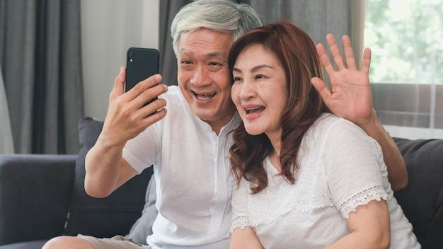 アジアのシニアカップルの自宅でのビデオ通話。アジアのシニア中国の祖父母、ホームコンセプトのリビングルームのソファに横たわっている間家族の孫の子供と話している携帯電話のビデオ通話を使用して。 無料写真