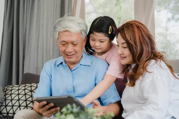 アジアの祖父母と孫娘が自宅でタブレットを使用しています。シニア中国人、おじいちゃん、おばあちゃんが幸せな家族の時間を過ごす若い女の子のリビングルームのコンセプトでソファに横たわって、ソーシャルメディアをチェック 無料写真