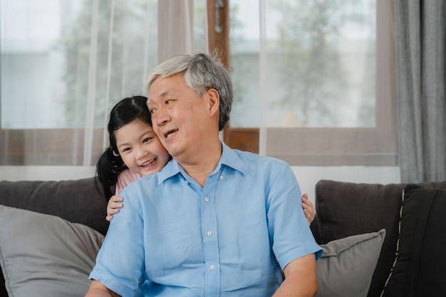 アジアの祖父が自宅で孫娘と話しています。シニア中国人、幸せなおじいちゃんは、家族の時間を使用して若い孫娘の女の子とリラックスし、リビングルームのソファーに横になっている若い女の子の子供とリラックスします。 無料写真