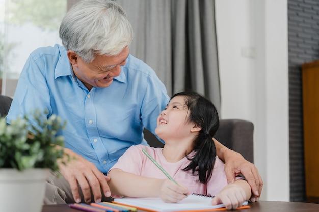 アジアの祖父は、孫娘の描画と自宅で宿題をすることを教えます。シニア中国人、おじいちゃんは、ホームコンセプトのリビングルームのソファーに横になっている若い女の子とリラックスします。 無料写真