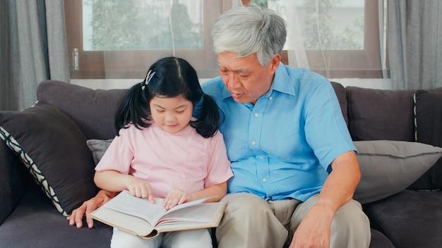 アジアの祖父は家でくつろいでいます。シニア中国人、幸せなおじいちゃんと若い孫娘の女の子は本を読んで楽しんで、リビングルームのコンセプトで一緒に宿題をします。 無料写真