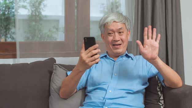 自宅でアジアの年配の男性のビデオ通話。ホームコンセプトのリビングルームのソファに横たわっている間家族の孫の子供と話している携帯電話のビデオ通話を使用してアジアのシニアの古い中国人男性。 無料写真
