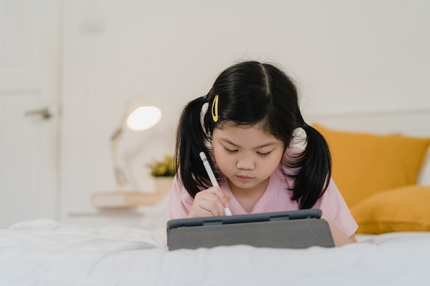 自宅で描く若いアジアの女の子。アジア日本人女性子供子供は、ベッドの上に横たわる寝る前にスケッチブックで楽しい楽しい幸せ漫画をリラックス、夜のコンセプトで寝室で快適さと落ち着きを感じるリラックスします。 無料写真